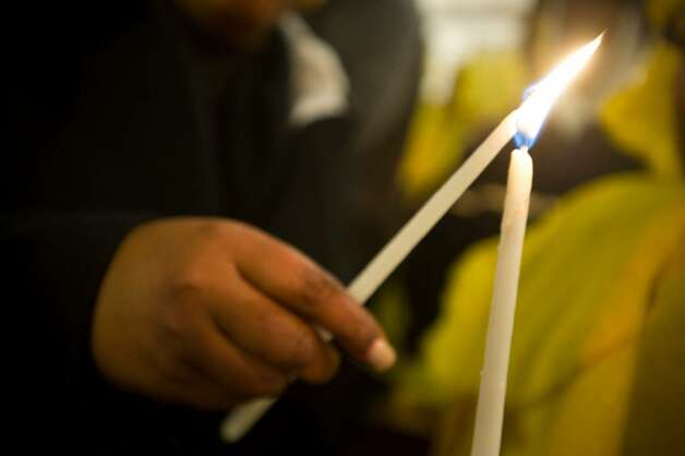 A woman lights a candle before a candlelight march for the victims of the earthquake in Haiti from downtown Stamford to the Haitian American Catholic Center on Hope St. in Stamford, Conn. on Sunday, Jan. 17 2009. Photo: Chris Preovolos / Stamford Advocate