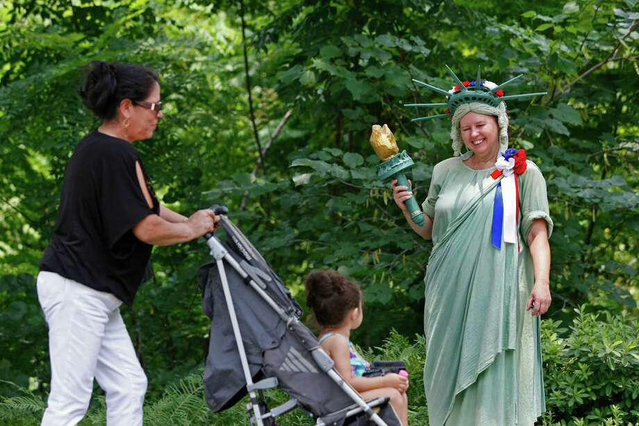 Sue Canup, dressed as the Statue of Liberty, greets Maria Macias and her granddaughter, Sophia, 2, as Bayou Bend celebrated Independence Day Thursday, July 4, 2013, in Houston.  The event included a reading of the Declaration of Independence, a jazz ban and activities for children. Photo: Johnny Hanson, Houston Chronicle / © 2013  Houston Chronicle