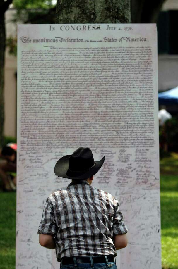 Frank Braun, signs a replica of the Declaration of Independence as Bayou Bend celebrated Independence Day Thursday, July 4, 2013, in Houston. 