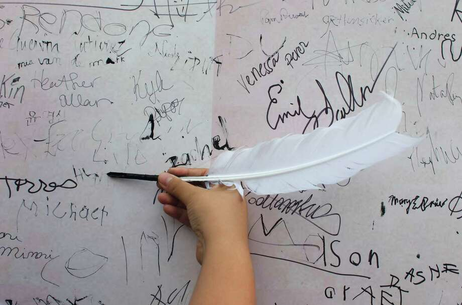 Hunter Almanza, 9, writes his name with a feather marker on a replica of the Declaration of Independence as Bayou Bend celebrated Independence Day Thursday, July 4, 2013, in Houston. 