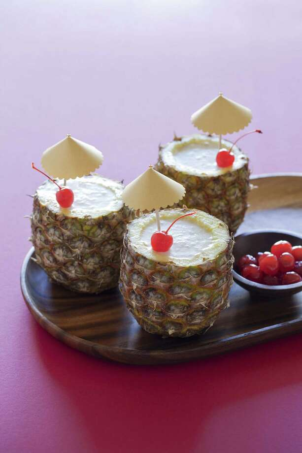 "A recipe for piña coladas served in pineapple shells is featured in ""Cocktails for a Crowd"" by Kara Newman. Newman also offers recipes for maraschino cherries and other garnishes. Photo: Photos Courtesy Teri Lyn Fisher"