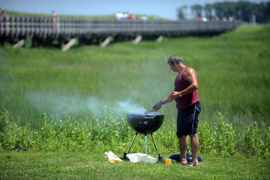 Kadri Bajrami, of Waterbury, enjoys a barbecue with family at Silver Sands State Park in Milford, Conn. Wednesday, July 4, 2013. Photo: Autumn Driscoll / Connecticut Post