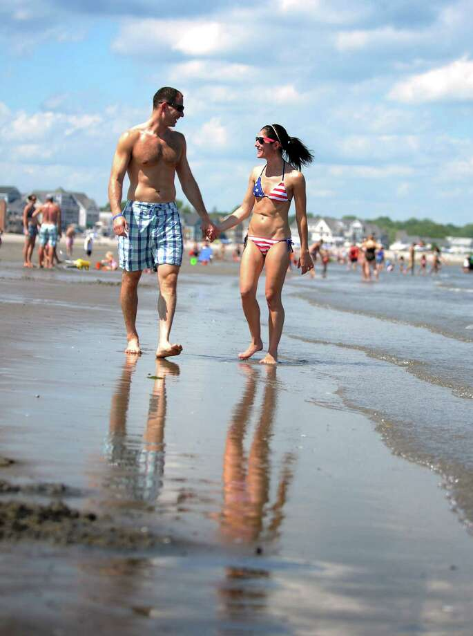 Michael Drazin, of Greenwich, and Taryn Porzio, of Stamford, walk the beach Wednesday, July 4, 2013 at Silver Sands State Park in Milford, Conn. Photo: Autumn Driscoll / Connecticut Post
