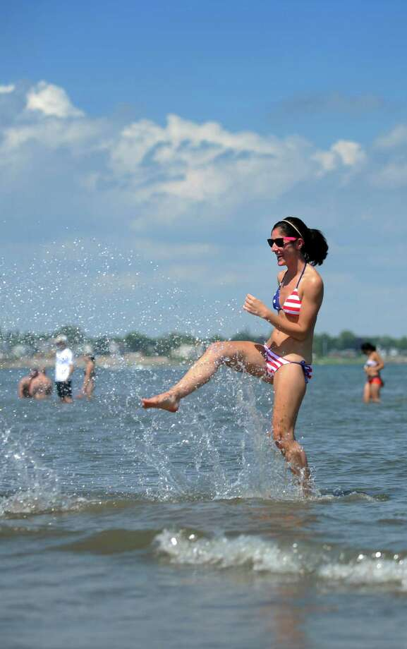 Taryn Porzio, of Stamford, splashes her boyfriend during a walk along the shore Wednesday, July 4, 2013 at Silver Sands State Park in Milford, Conn. Photo: Autumn Driscoll / Connecticut Post