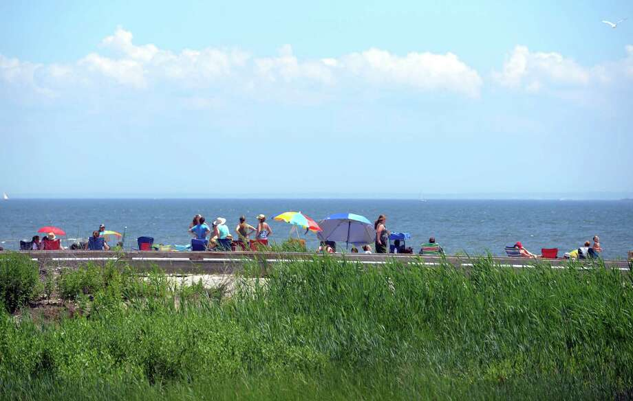 People enjoy a hot holiday Wednesday, July 4, 2013 at Silver Sands State Park in Milford, Conn. Photo: Autumn Driscoll / Connecticut Post