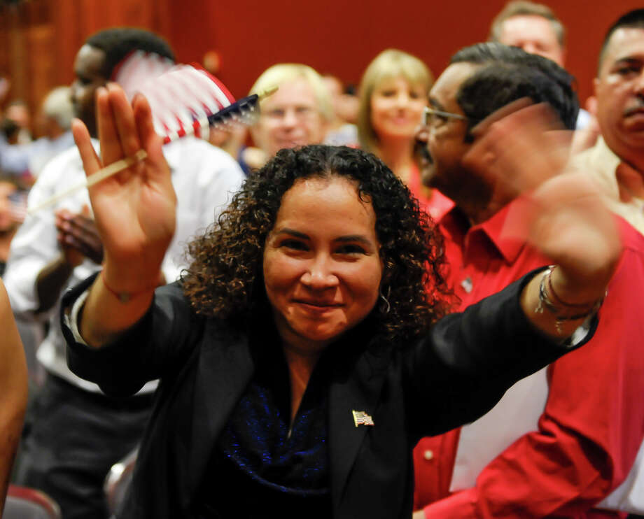 Yanira Villeda waves after being after taking the Naturalization Oath during ceremonies Thursday afternoon at the Henry B. Gonzalez Convention Center. Photo: Robin Jerstad