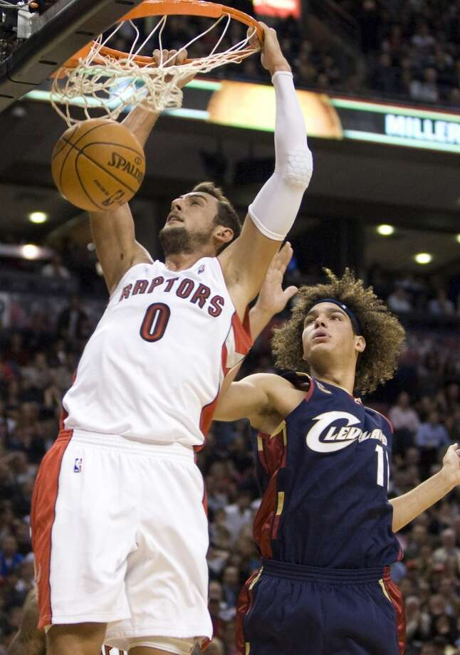 Toronto Raptors guard Marco Belinelli (0) slams home a dunk in front of Cleveland Cavaliers forward Anderson Varejao (17) during the first half an NBA basketball game in Toronto on Wednesday, Oct. 28, 2009.