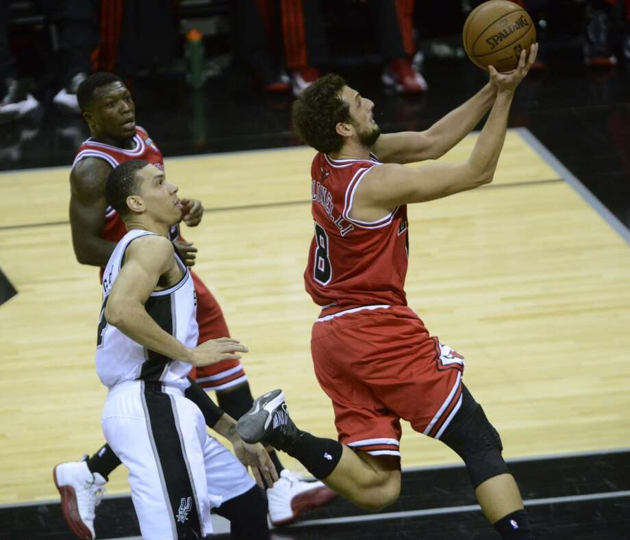 Marco Belinelli of the Chicago Bulls drives by Danny Green of the San Antonio Spurs during NBA action at the AT&T Center on Wednesday, March 6, 2013.
