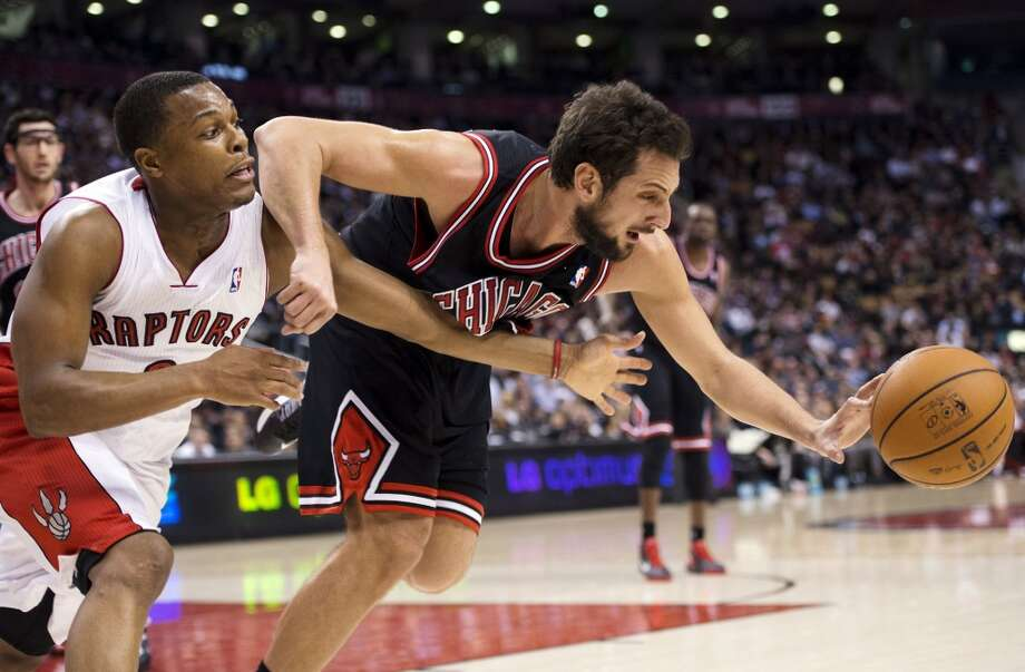 Toronto Raptors guard Kyle Lowry, left, battles for the ball against Chicago Bulls guard Marco Belinelli during the first half of their NBA basketball game, Wednesday, Jan. 16, 2013, in Toronto.