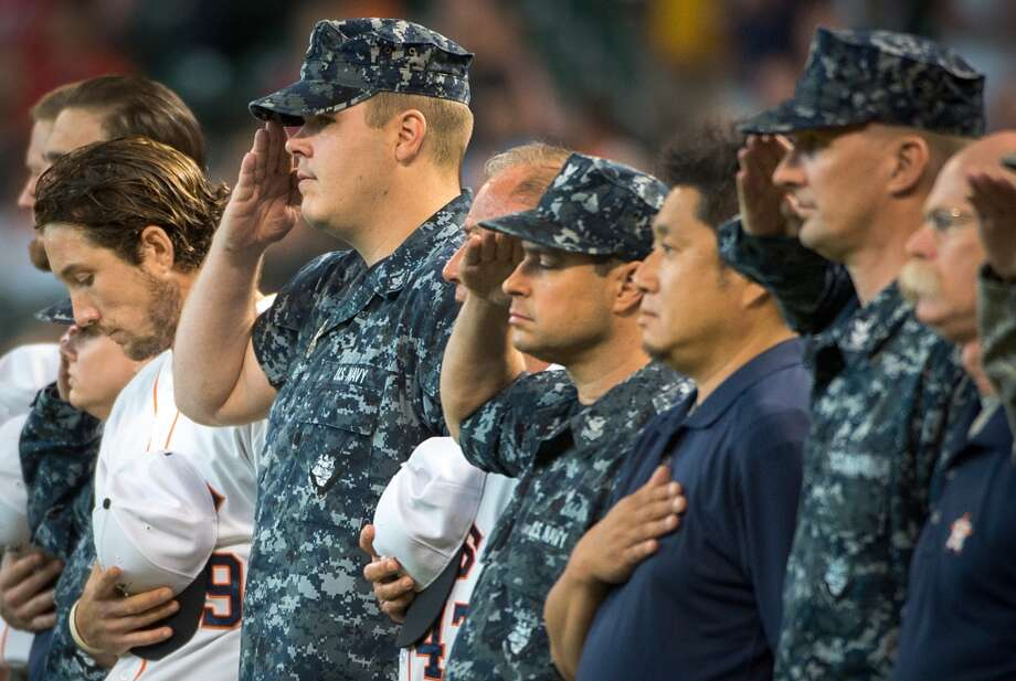 Astros infielder Brett Wallace, left, stands with U.S. military members for the national anthem during ceremonies before the game.