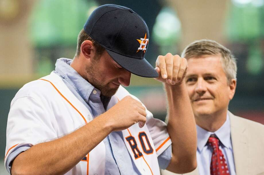 Astros third-round draft pick Kent Emanuel dons an Astros cap as he is introduced during the fifth inning. Emanuel, a left-handed pitcher from North Carolina, signed with the team for a reported $747,700 on Thursday. Astros GM Jeff Luhnow looks on at right.