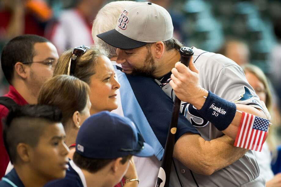 Rays designated hitter Luke Scott hugs a man in the crowd before the game.