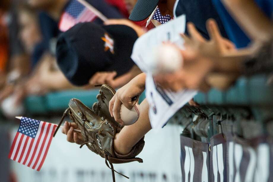 A fan holds a small American flag as they try to get autographs before the game.