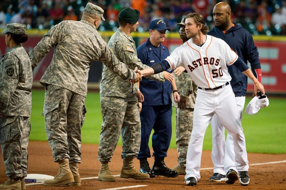 Astros relief pitcher Josh Fields shakes hands with U.S. military members during ceremonies before the game.
