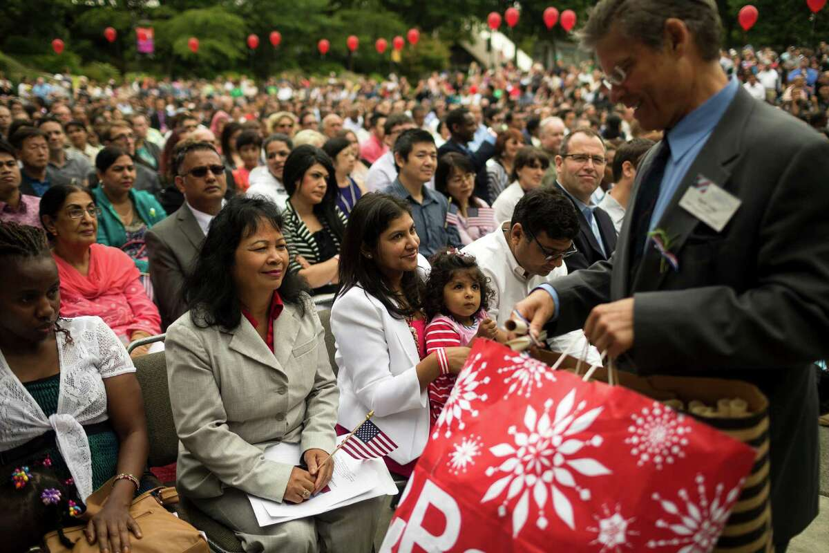 Candidates receive flags and scrolls at the beginning of the 29th Annual Naturalization Ceremony Thursday, July 4, 2013, in the Seattle Center Fisher Pavilion in Seattle. The event, hosted by the Ethnic Heritage Council, brought 490 candidates from 87 countries and nations to swear in as U.S. citizens.