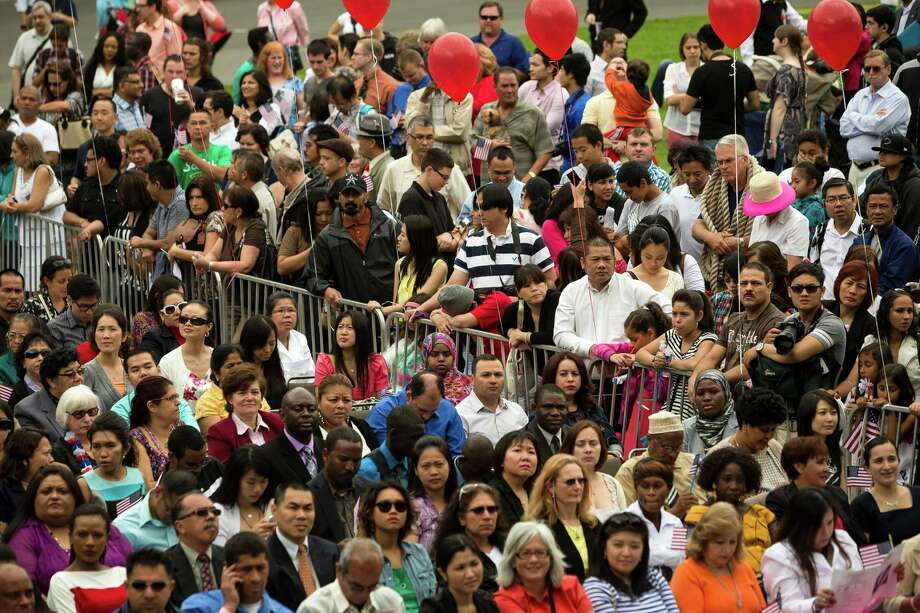 Hundreds of friends, family members and onlookers packed around a barrier to watch the 29th Annual Naturalization Ceremony Thursday, July 4, 2013, in the Seattle Center Fisher Pavilion in Seattle. The event, hosted by the Ethnic Heritage Council, brought 490 candidates from 87 countries and nations to swear in as U.S. citizens. Photo: JORDAN STEAD, SEATTLEPI.COM / SEATTLEPI.COM
