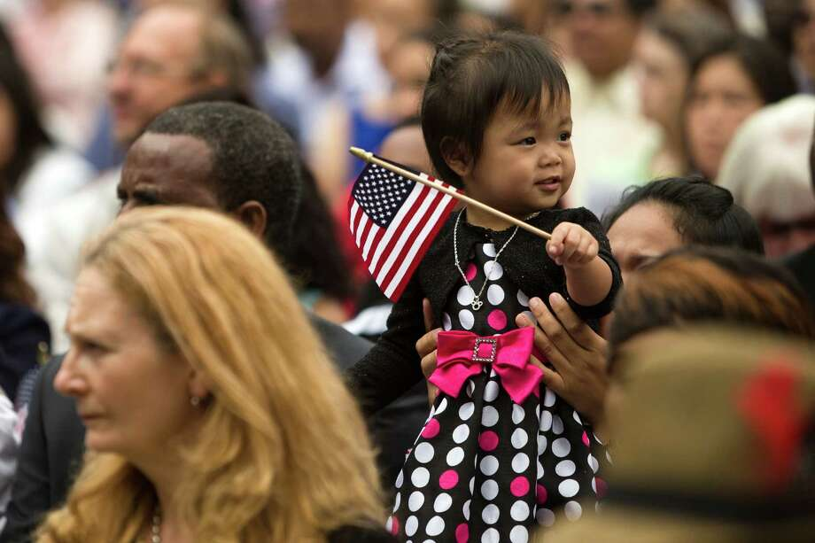 A young child waves a flag during the 29th Annual Naturalization Ceremony Thursday, July 4, 2013, in the Seattle Center Fisher Pavilion in Seattle. The event, hosted by the Ethnic Heritage Council, brought 490 candidates from 87 countries and nations to swear in as U.S. citizens. Photo: JORDAN STEAD, SEATTLEPI.COM / SEATTLEPI.COM