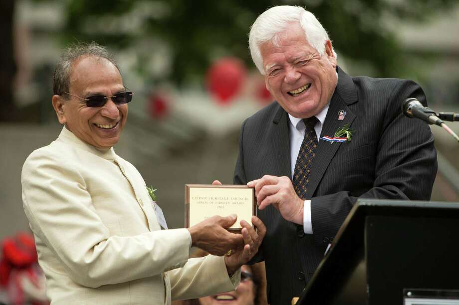 United States Representative Jim McDermott, right, presents Jagdish Sharma, left, with the Spirit of Liberty Award at the 29th Annual Naturalization Ceremony Thursday, July 4, 2013, in the Seattle Center Fisher Pavilion in Seattle. The event, hosted by the Ethnic Heritage Council, brought 490 candidates from 87 countries and nations to swear in as U.S. citizens. Photo: JORDAN STEAD, SEATTLEPI.COM / SEATTLEPI.COM
