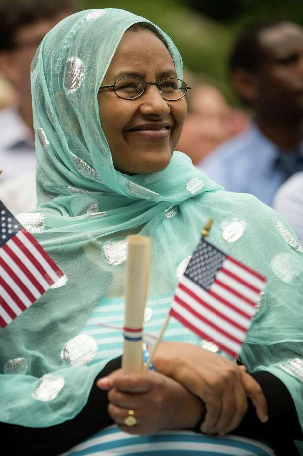 Candidate Giftle Hassen holds a flag while listening to keynote speakers during the 29th Annual Naturalization Ceremony Thursday, July 4, 2013, in the Seattle Center Fisher Pavilion in Seattle. The event, hosted by the Ethnic Heritage Council, brought 490 candidates from 87 countries and nations to swear in as U.S. citizens. Photo: JORDAN STEAD, SEATTLEPI.COM / SEATTLEPI.COM