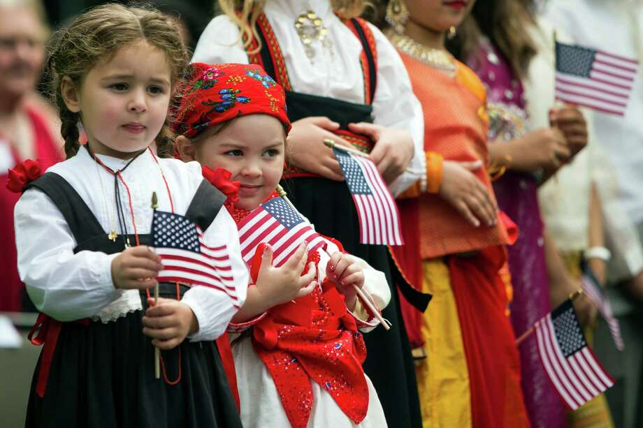 Young women representing different cultures take the stage at the 29th Annual Naturalization Ceremony Thursday, July 4, 2013, in the Seattle Center Fisher Pavilion in Seattle. The event, hosted by the Ethnic Heritage Council, brought 490 candidates from 87 countries and nations to swear in as U.S. citizens. Photo: JORDAN STEAD, SEATTLEPI.COM / SEATTLEPI.COM