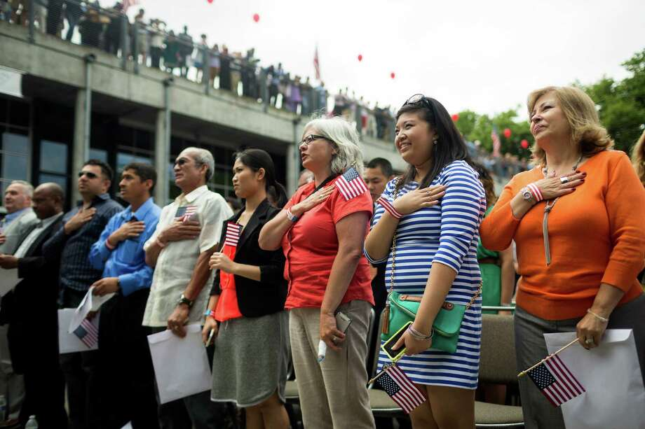 Candidates take the oath during the swearing in at the 29th Annual Naturalization Ceremony Thursday, July 4, 2013, in the Seattle Center Fisher Pavilion in Seattle. The event, hosted by the Ethnic Heritage Council, brought 490 candidates from 87 countries and nations to swear in as U.S. citizens. Photo: JORDAN STEAD, SEATTLEPI.COM / SEATTLEPI.COM