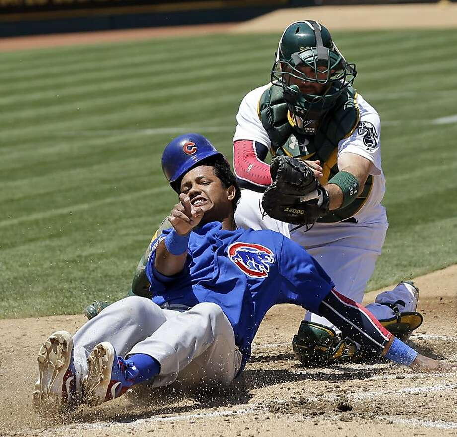 Chicago Cubs' Starlin Castro, left, is tagged out at the plate by Oakland Athletics catcher Derek Norris as he tried to score from second base on a single by Alfonso Soriano during the fourth inning of an MLB baseball game on Thursday, July 4, 2013 in Oakland, Calif. (AP Photo/Marcio Jose Sanchez) Photo: Marcio Jose Sanchez, Associated Press