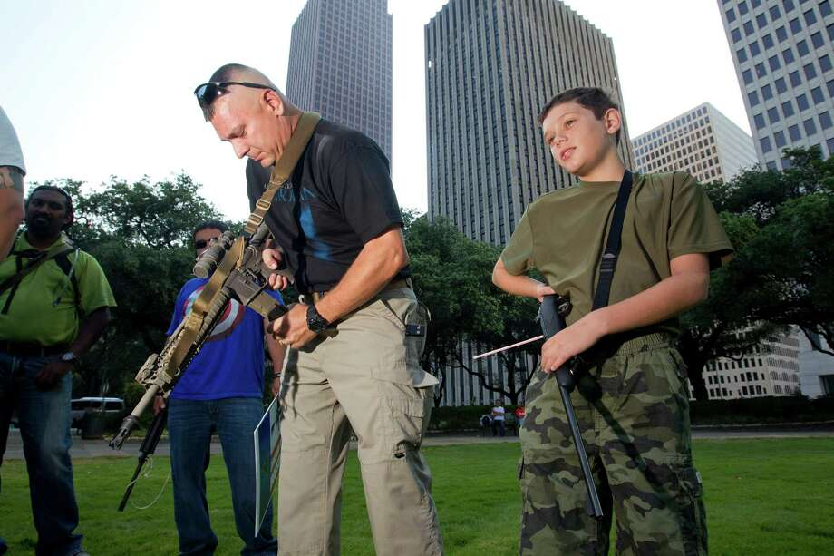 Ed Aldredge of Sugar Land makes sure there's no round in the chamber of his AR-15, or in his son Austin's .22-caliber rifle, as they joined a group of some two dozen demonstrators with the gun-rights group Come and Take it Houston. Photo: Johnny Hanson, Staff / © 2013  Houston Chronicle