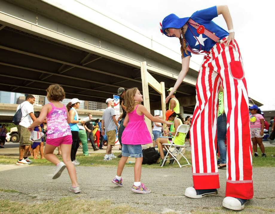 Jamie Hedden, on silts, greets visitors to the Freedom over Texas festival at Eleanor Tinsley Park Thursday, July 4, 2013, in Houston. Photo: Brett Coomer, Houston Chronicle / © 2013 Houston Chronicle