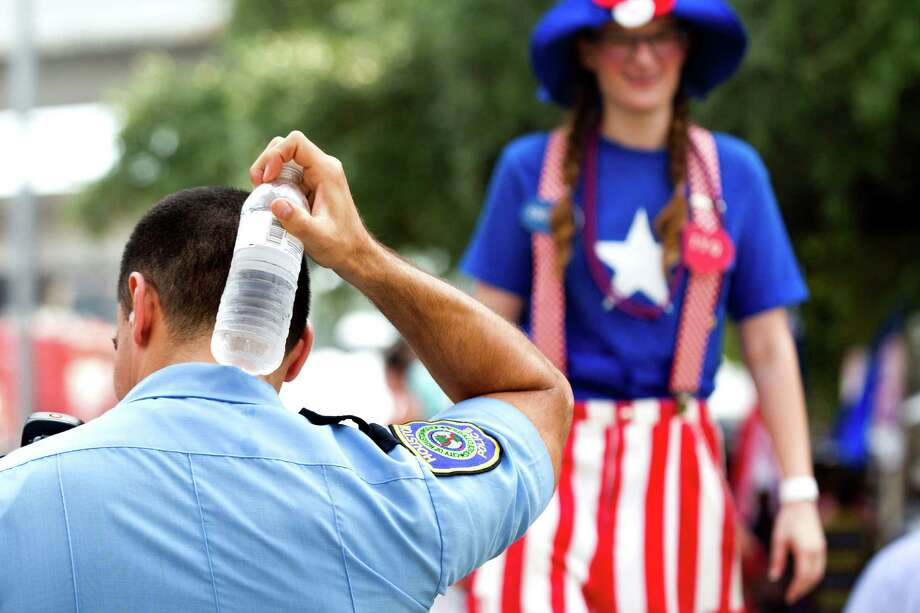 A Houston police officer uses a water bottle to cool off as he patrols during the Freedom over Texas festival at Eleanor Tinsley Park Thursday, July 4, 2013, in Houston. Photo: Brett Coomer, Houston Chronicle / © 2013 Houston Chronicle