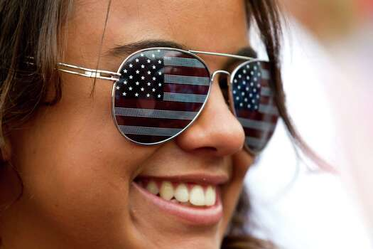 Fabiana Lima, a visitor to Houston from Brazil, wears American flag sunglasses during the Freedom over Texas festival at Eleanor Tinsley Park Thursday, July 4, 2013, in Houston. Photo: Brett Coomer, Houston Chronicle / © 2013 Houston Chronicle