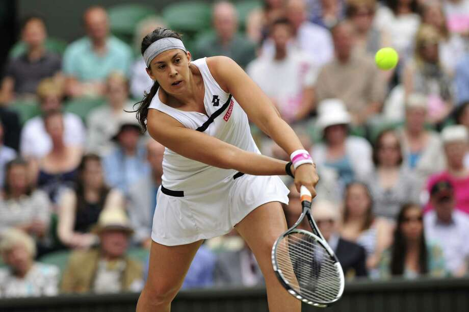 France's Marion Bartoli returns against Belgium's Kirsten Flipkens during their women's singles semi-final match on day ten of the 2013 Wimbledon Championships tennis tournament at the All England Club in Wimbledon, southwest London, on July 4, 2013.  AFP PHOTO / GLYN KIRK  -  RESTRICTED TO EDITORIAL USEGLYN KIRK/AFP/Getty Images ORG XMIT: 3275 Photo: GLYN KIRK / AFP