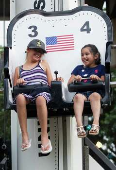 Kayla, 8, and Dezilynn Rodriguez, 5, (not related) ride the Rascal Rocket in the Kids Zone during the Freedom Over Texas festival at Eleanor Tinsley Park on Thursday, July 4, 2013, in Houston. Photo: J. Patric Schneider, For The Chronicle / © 2013 Houston Chronicle