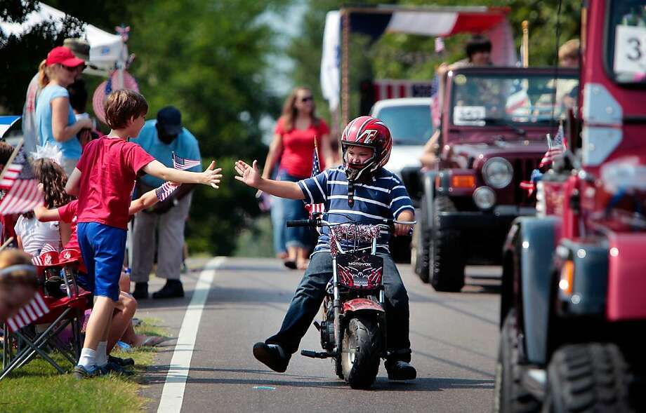 Patrick Ardis, 10, gets a high-five from his friend Porter Rosenberg, 10, left, while riding in the Cordova Independence Day Parade at the Cordova Community Center in Cordova, Tenn., on Thursday, July 4, 2013. Photo: Jim Weber, Associated Press
