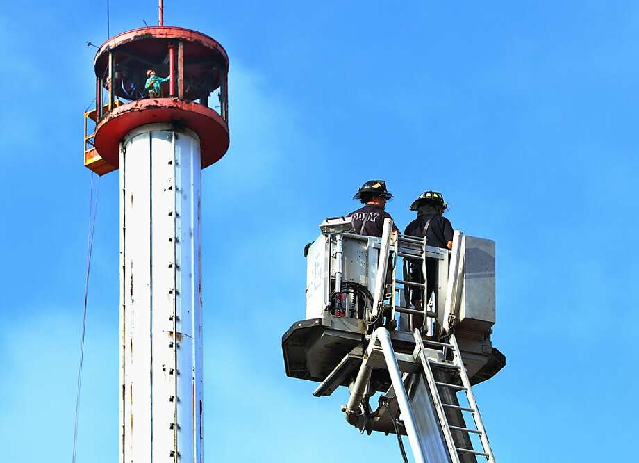NEW YORK, NY- JULY 04: Firemen look on as workers disassemble the Astrotower in Coney Island on July 4, 2013 in the borough of Brooklyn in New York City. Officials decided to close Luna Park and sections of the boardwalk while workers take down the amusement tower which was seen precariously swaying two days ago.  (Photo by Monika Graff/Getty Images) *** BESTPIX *** Photo: Monika Graff, Getty Images