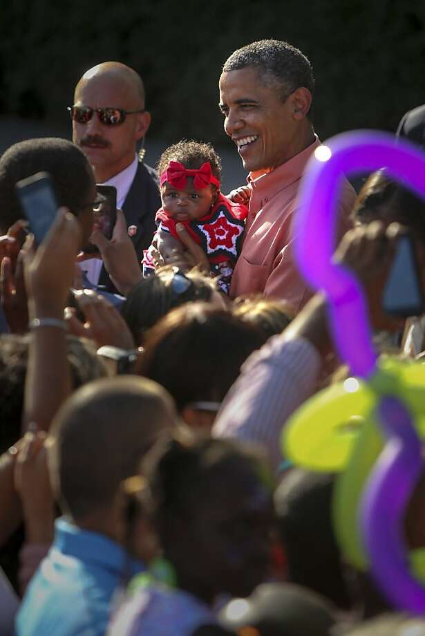 President Barack Obama holds an infant while greeting guests at the White House during a Fourth of July celebration, in Washington, July 4, 2013. (Allison Shelley/The New York Times) Photo: Allison Shelley, New York Times