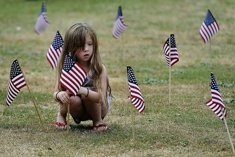 Victoria Costa, 5, plants a flag in the middle of a patriotic display Thursday, July 4, 2013, during the annual Freedom Festival celebration in Nacogdoches, Texas.  Photo: Andrew D. Brosig, Associated Press