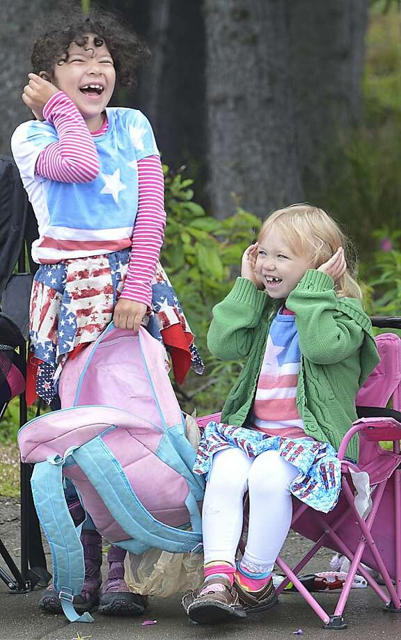 Destiny Dysert and Olyve Croom laugh and cover their ears as a fire truck rumbles by during the annual Fourth of July parade in Kenai, Alaska. Photo: Rashah McChesney, Associated Press