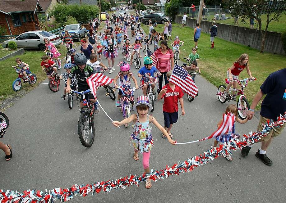 Kamryn Posten, 8, foreground center, leads a parade, Thursday, July 4, 2013 during Fourth of July celebrations in Keyport, Wash. Photo: Larry Steagall, Associated Press