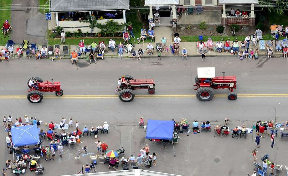 People line North State Street while watching a row of tractors in the Annual Millville Independence Day Parade, Thursday, July 4, 2013, in Millville, Pa. (AP Photo/Bloomsburg Press Enterprise, Jimmy May) Photo: Jimmy May, Associated Press