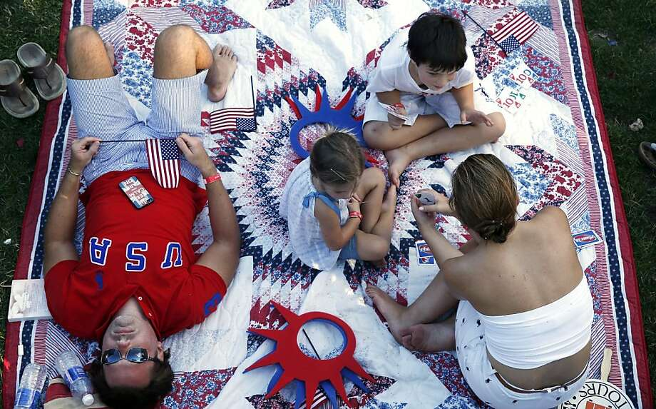 The Walker family of Lafayette, La. relaxes while waiting for the start of the Boston Pops Fourth of July Concert at the Hatch Shell in Boston, Thursday, July 4, 2013.  Photo: Michael Dwyer, Associated Press