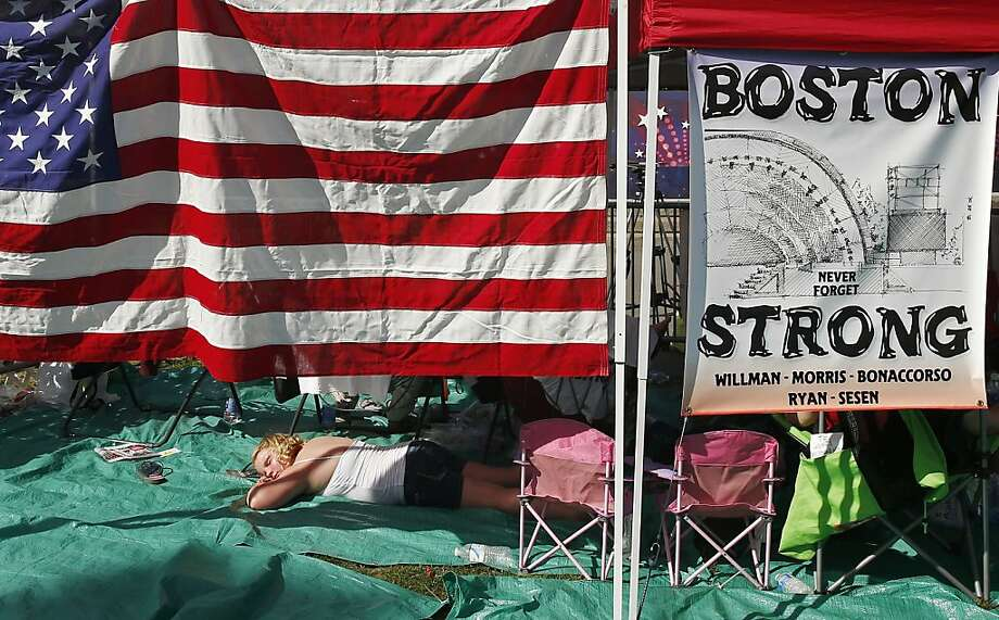 Alexis Morris, 12, of Gloucester, Mass., sleeps under a tent with a display in honor of the victims of the Boston Marathon bombings while waiting for the Boston Pops Fourth of July Concert to start at the Hatch Shell in Boston, Thursday, July 4, 2013. (AP Photo/Michael Dwyer) Photo: Michael Dwyer, Associated Press