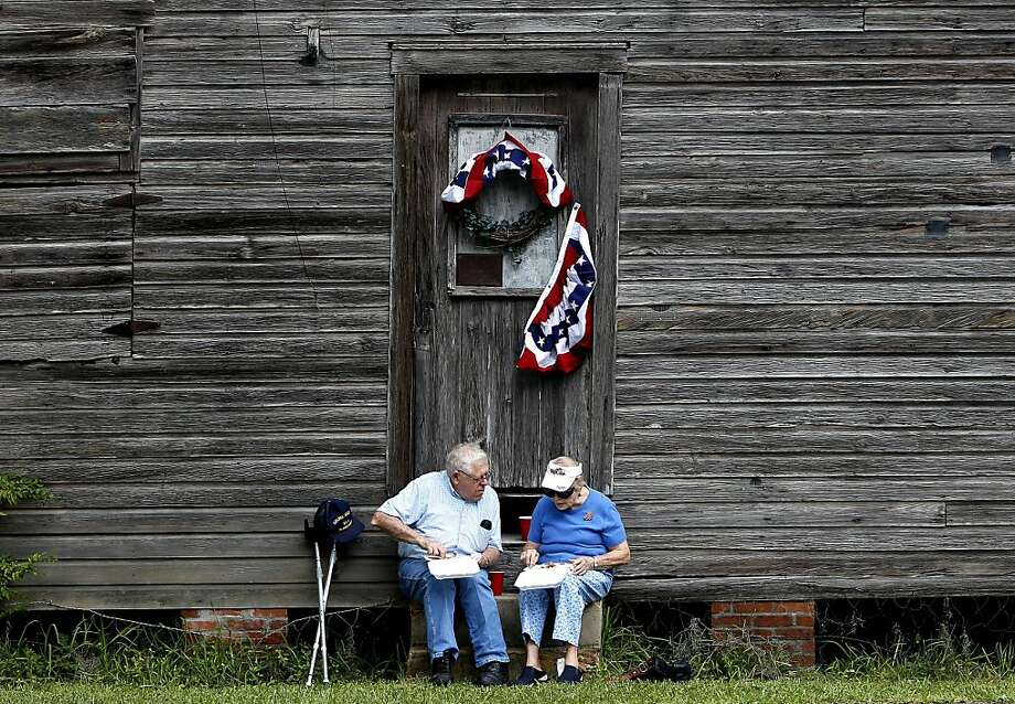 Robert and Gena Phillips eat fried fish, coleslaw and hushpuppies following the annual Independence Day parade on Thursday, July 4, 2013 in Micanopy, Fla. (AP Photo/The Gainesville Sun, Matt Stamey) Photo: Matt Stamey, Associated Press
