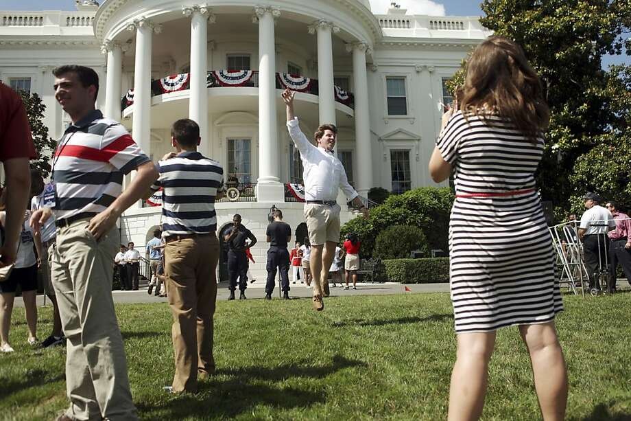 Robin Muthig, right, snaps a photo of Bob Philips, center, on the South Lawn of the White House before the start of a Fourth of July celebration, in Washington, July 4, 2013. (Allison Shelley/The New York Times) Photo: Allison Shelley, New York Times