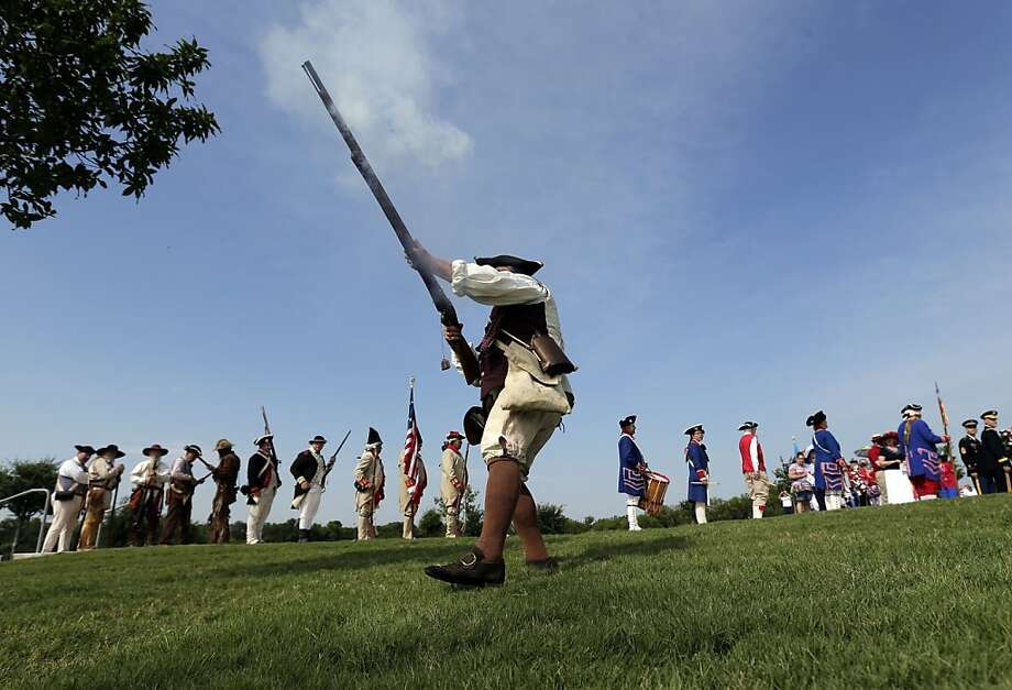 "Ed Lunderman, a member of a Living History Musket Detail, fires his musket to represent ""the Shot Heard Around the World"" during a Fourth of July Patriotic Ceremony at Fort Sam Houston National Cemetery, Thursday, July 4, 2013, in San Antonio. (AP Photo/Eric Gay) Photo: Eric Gay, Associated Press"