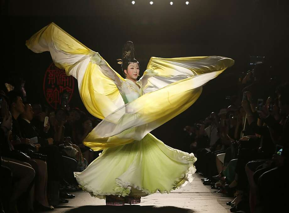 Chinese singer Li Yugang performs and wears a creation by Chinese fashion designer Lawrence Xu during her Women's Fall Winter 2013 haute couture fashion collection in Paris, France, Thursday, July 4, 2013. (AP Photo/Jacques Brinon) Photo: Jacques Brinon, Associated Press
