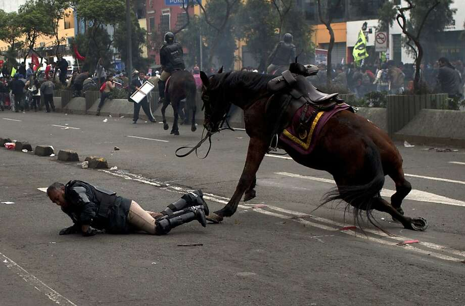 A policeman tries to recover after falling from his horse during a protest against the new civil service law that will require government employees to undergo work evaluations, in Lima, Peru, Thursday, July 4,  2013. After a total of 20 hours of debates and months of modifications, Peru's Congress approved the new civil service law with 59 votes in favor, 45 against and 3 abstentions. (AP Photo/Rodrigo Abd) Photo: Rodrigo Abd, Associated Press