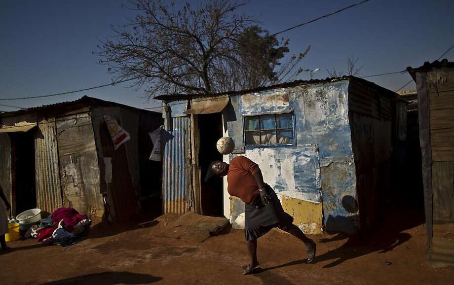 A South African woman, bounces the ball on her head while playing with a football with other women, not seen, next to their homes in a Soweto township on the outskirts of Johannesburg, South Africa, Thursday, July 4, 2013. (AP Photo/Muhammed Muheisen) Photo: Muhammed Muheisen, Associated Press