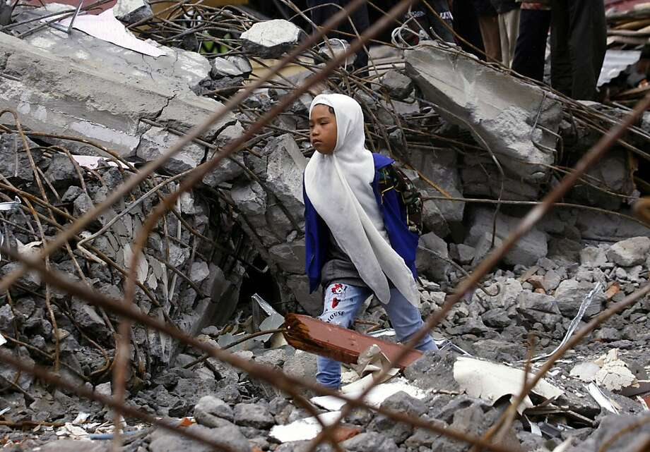 A young Acehnese girl walks among the rubble of a mosque destroyed by Tuesday's earthquake in Blang Mancung, Aceh province, Indonesia, Thursday, July 4, 2013. The death toll from the earthquake that hit Indonesia's Aceh province earlier this week has reached 30, and police and soldiers are searching the debris for another 12 people believed missing, officials said Thursday.  (AP Photo/Binsar Bakkara) Photo: Binsar Bakkara, Associated Press