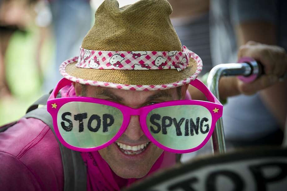 "A human rights activists wears pink glasses reading ""stop spying"" during a protest against the alleged violation of privacy by the US National Security Agency at McPherson square in downtown Washington DC, July 04, 2013. The recent leaking of  classified intelligence documents has led to revelations that the US is systematically seizing vast amounts of phone and web data.  TOPSHOTS/AFP PHOTO / MLADEN ANTONOVMLADEN ANTONOV/AFP/Getty Images Photo: Mladen Antonov, AFP/Getty Images"