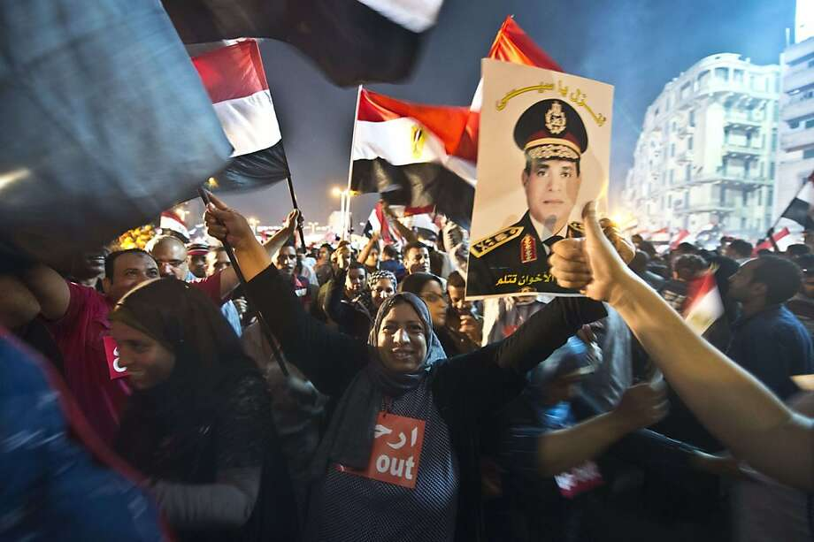 TOPSHOTS People celebrate at Tahrir Square with a portrait of Army chief Abdel Fattah al-Sisi after a broadcast confirming that the army will temporarily be taking over from the country's first democratically elected president Mohammed Morsi on July 3, 2013 in Cairo. In their tens of thousands, they cheered, ignited firecrackers and honked horns as soon as the army announced President Mohamed Morsi's rule was over, ending Egypt's worst crisis since its 2011 revolt. AFP PHOTO / KHALED DESOUKIKHALED DESOUKI/AFP/Getty Images Photo: Khaled Desouki, AFP/Getty Images